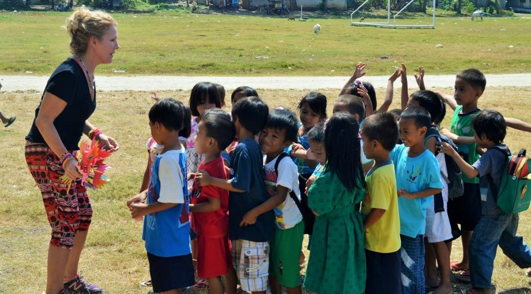A volunteer coaching sports in the Philippines prepares for a fun activity with children
